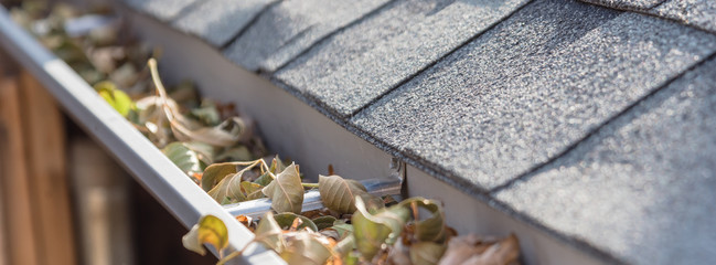 Panoramic view gutter full of dried leaves near roof shingles with satellite dish in background