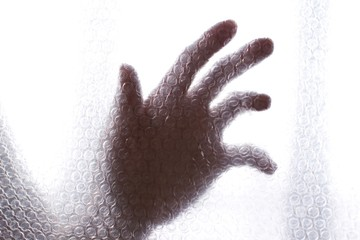 young womans hand behind a transparent air bubble plastic wrap