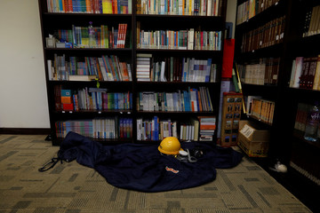 A helmet, gas mask, and sleeping of a protester is left behind in the library of in Hong Kong Polytechnic University (PolyU) in Hong Kong