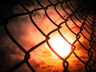 The sunset and red sky be hide metal-chain link fencing