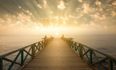 Wooden pier on sea at morning sunrise