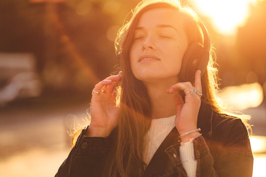 Stylish fashionable happy hipster woman teen enjoys music in wireless headphones while walking around the city at sunset