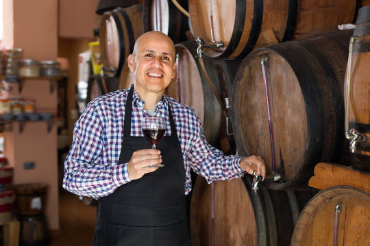 Laughing male wine maker taking wine from wood