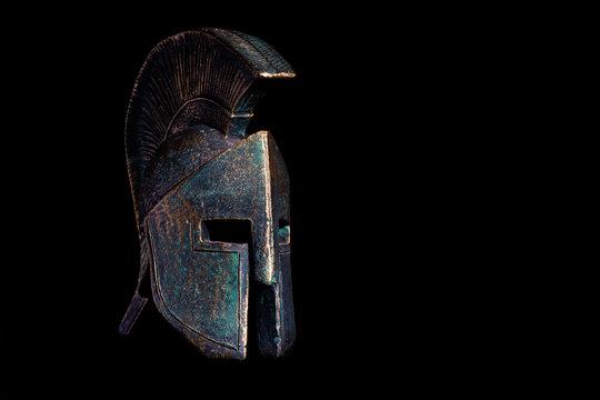 Ancient Spartan bronze helmet on black background