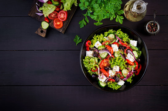 Healthy food. Greek salad with cucumber, tomato, sweet pepper, lettuce, red onion, feta cheese and olives.  Top view, copy space