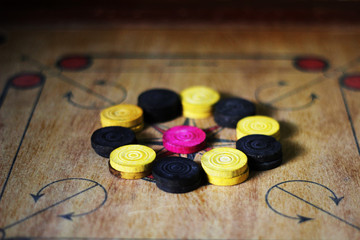 A game of carom set and ready to play.A game of carrom with pieces carrom man on the board carrom.Carom board game, selective focus.