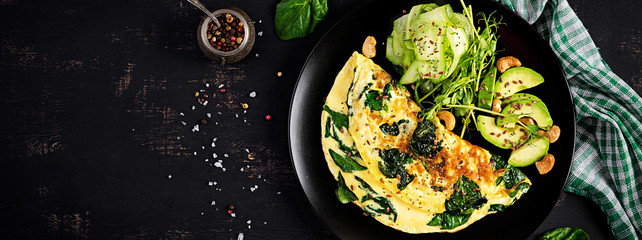Ketogenic, paleo diet breakfast. Omelette with spinach and avocado, cucumber. Top view, banner