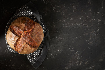 Freshly baked Artisan sourdough bread loaves with kitchen towel on black concrete backgroun