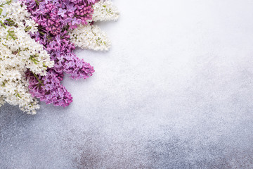 Poster Lilac Branches of purple lilac on stone background. Romantic spring mood. Top view. Copy for your text. Horizontal banner - Image