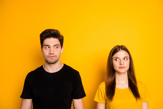Photo of suspicious thinking pondering couple uncertain about each other looking suspiciously suspecting isolated over vibrant shiny color background
