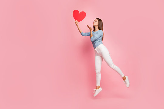 Full length body size side brown haired profile photo of cheerful positive cute pretty nice tender girl sending air kiss to heart held isolated pastel color background