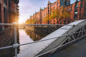 Arch bridge over canals in the Speicherstadt of Hamburg, Germany, Europe. Historical red brick building lit by warm soft golden sunset light