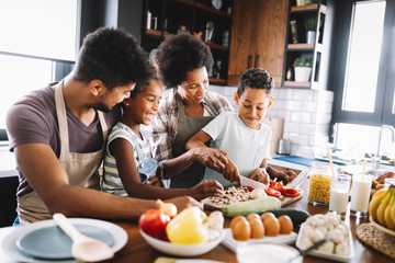 Happy african american family preparing healthy food together in kitchen