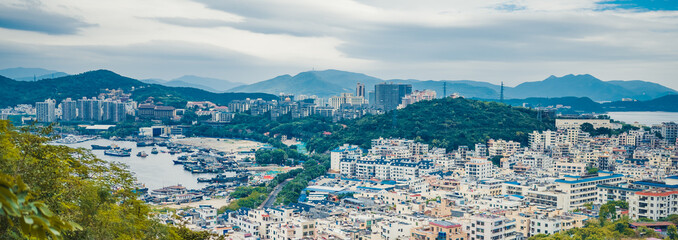 Top View of Hainan's Sanya City, with local houses and luxury hotels and buildings. Summer Vacation Paradise in Asia.