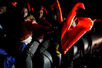 Migrants receive life vest during a search and rescue operation by the NGO Proactiva Open Arms rescue boat in the central Mediterranean Sea