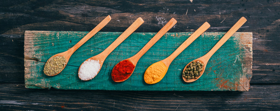 flat lay of colorful spices in spoons on wooden table