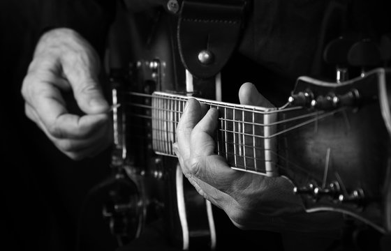 Guitarist hands and guitar close up. playing electric guitar black and white.