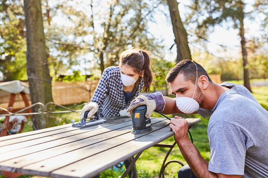 Couple doing home improvement in the garden with grinder