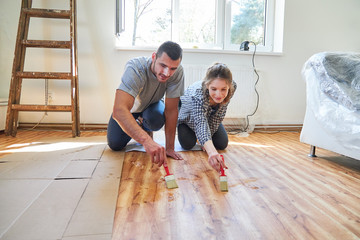 Couple at the parquet paint at renovation