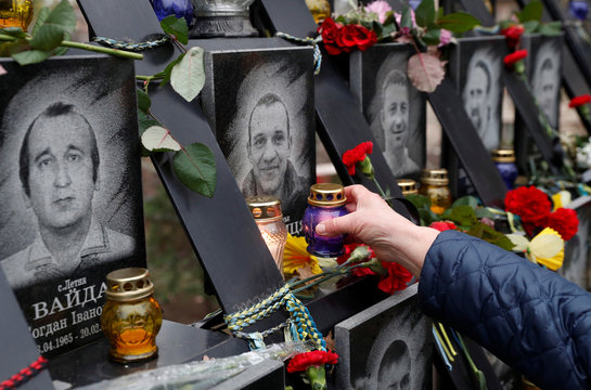 """A woman places a candle during a commemoration ceremony at a monument to the so-called """"Heavenly Hundred"""" to mark the sixth anniversary of the start of the anti-government uprising in Kiev"""
