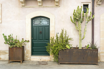 Façade of typical town house with green cactuses and old door in a Mediterranean city (Syracuse) on Sicily, Italy