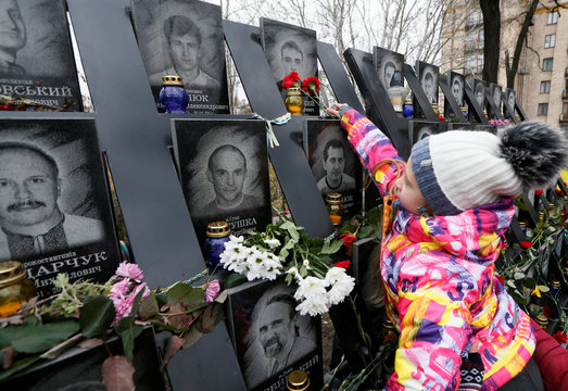 """A girl lays flowers during a commemoration ceremony at a monument to the so-called """"Heavenly Hundred"""" to mark the sixth anniversary of the start of the anti-government uprising in Kiev"""
