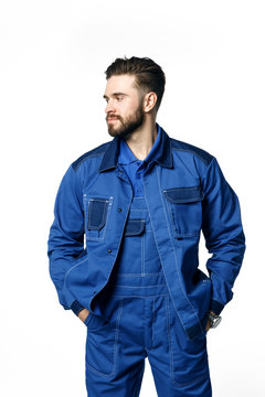 Young handsome man with a beard in a blue working uniform for cleaning rooms isolated on white background.