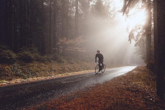 Rennradfahrer im Wald bei herbstlichem Wetter mit Sonnenstrahlen im Nebel