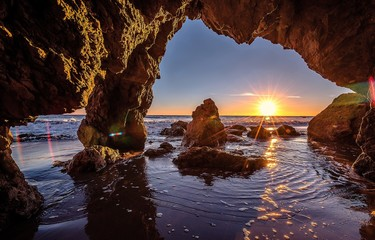 Foto op Plexiglas Bruin Beautiful and Colouful Orange Sunset beach of California with Rocks