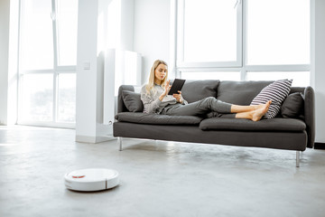 Woman relaxing on the couch while automatic vacuum cleaner doing the housework in the modern white living room. Household robots concept Wall mural