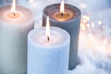 Dritter Advent - Drei brennende Adventskerzen im Schnee
