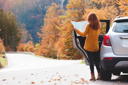girl with a map is standing near the car