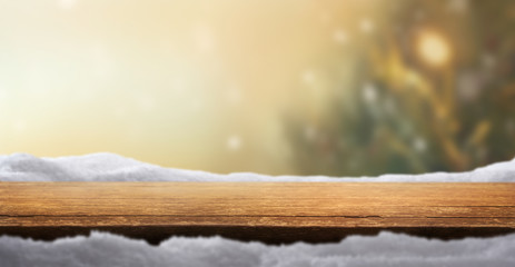 A Christmas tabletop product display background with snow and blurred Christmas tree and golden...