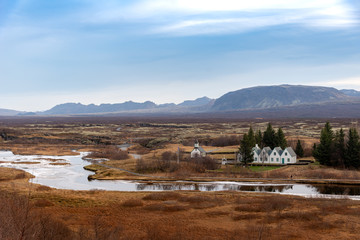 Beautiful scenery view at Thingvellir National Park in Iceland. It can see Pingvallakirkja church and water streaming from Pingvallavatn lake.