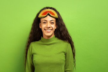 African-american young brunette woman's portrait in ski mask on green studio background. Concept of human emotions, facial expression, sales, ad, winter sport and holidays. Smiling, looks happy.