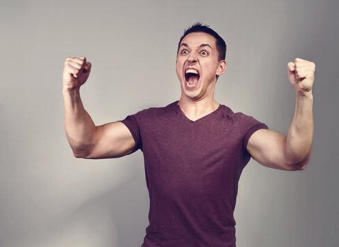 Excited shouting young casual man gesturing the hands in success celebrating sign with wide open mouth on grey background.