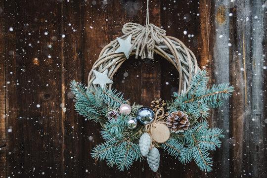Christmas wreath on rustic wooden door background of blue tree.
