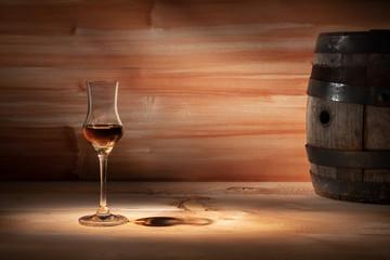 Grappa glass near an oak barrel