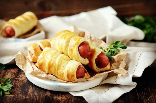 Sausages in the dough on a plate on a dark wooden table