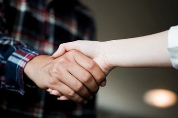 Closeup of male and female hands handshaking after effective negotiation showing mutual respect. Two people handshaking expressing respect and trust concept.