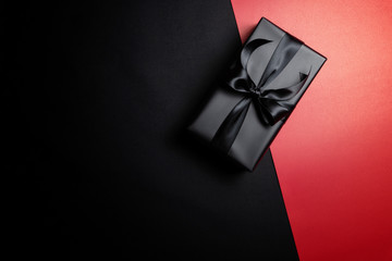 black gift box with black ribbons isolated on black background