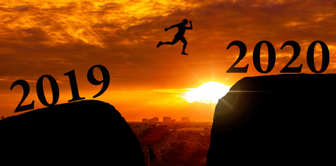 Silhouette of active young man jumping over to cliff and jump across between 2019 and 2020 word with sky sunset. Dark courage boy jump on light with feeling freedom. Concept celebrating new year. Wall mural