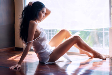 Attractive sexy woman wear white thin pajamas sitting behind window thinking about something. Charming lonely sexy girl feels relaxation in the room. Glamour women long hair slim body gets topless.