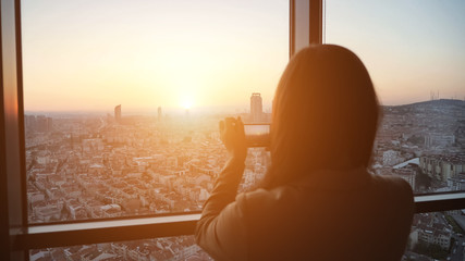 Silhouette of woman taking a pictures of panoramic city view at sunset on smartphone, focus on the city