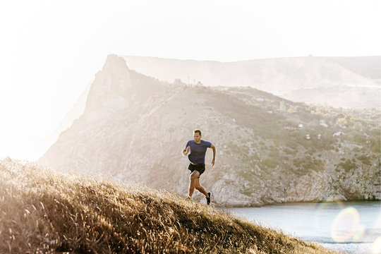 dynamic running uphill male runner in sunset light, mountains in sea bay