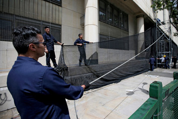 The facade of a courthouse is covered with plastic mesh, one day before a national strike in Bogota
