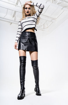 Attractive blonde woman with dark gothic makeup in leather skirt and knee-high boots posing on white background