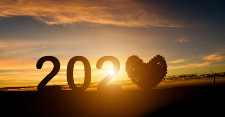 2020 new year concept. Silhouette of number include heart on the mountain at sunset background. Wall mural