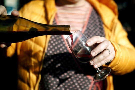 A woman pours a glass of Beaujolais Nouveau wine in a bistrot in Paris
