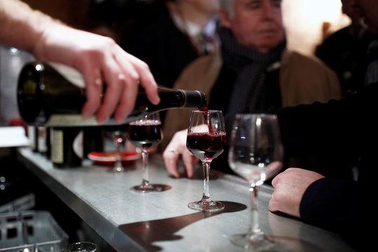 A barman pours a glass of Beaujolais Nouveau wine in a bistrot in Paris